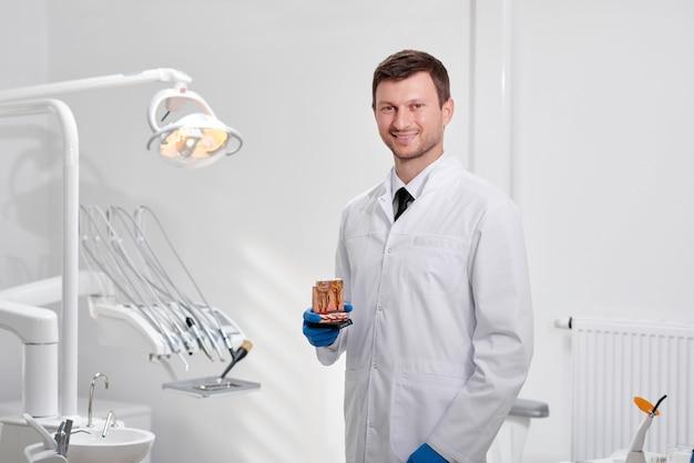 Portret van een volwassen mannelijke tandarts die trots op zijn kliniek stelt die tandenmodel houdt dat naar de camera glimlacht copyspace beroep beroep ervaring vertrouwen geneeskunde gezondheid tandheelkunde mondeling onderzoek.