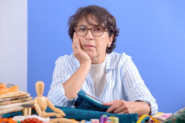 Portret van een volwassen naaister met een bril