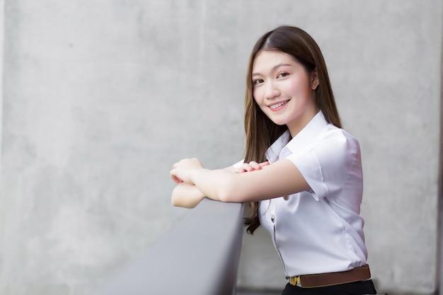 Portret van een volwassen thaise student in universitair studentenuniform. aziatisch mooi meisje zit gelukkig glimlachend op de universiteit