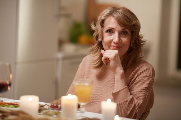 Portret van een volwassen vrouw camera kijken zittend aan de eettafel heeft ze diner