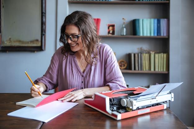 Portret van een volwassen vrouw journalist zitten aan de tafel