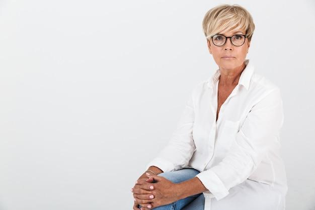 Portret van een volwassen vrouw met een bril die naar de camera kijkt terwijl ze geïsoleerd over een witte muur in de studio zit