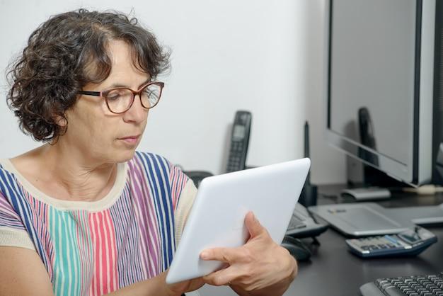 Portret van een volwassen vrouw met een digitale tablet