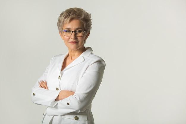 Portret van een volwassen vrouw met een kort kapsel met een bril in een witte jas