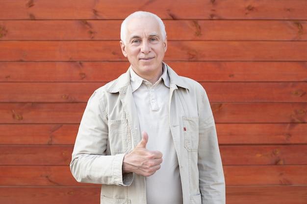 Portret van een volwassen zakenman op houten muur achtergrond. sluit omhoog gezicht van gelukkige succesvolle zakenman.