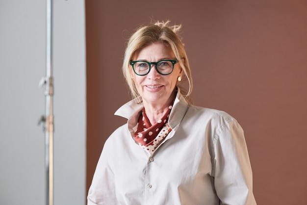Portret van een volwassen zakenvrouw in een wit overhemd en een bril die lacht naar de camera die op kantoor staat