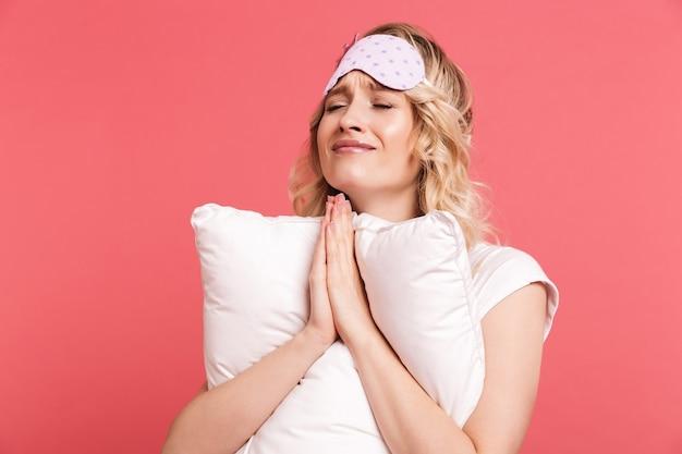 Portret van een vreedzame jonge vrouw die een slaapmasker draagt en op een wit kussen ligt dat over een rode muur wordt geïsoleerd