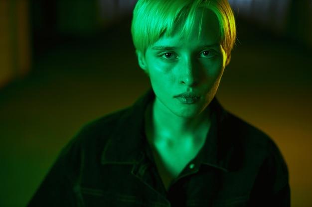 Portret van een vreemd meisje met kort blond haar dat recht in de moderne camera kijkt...