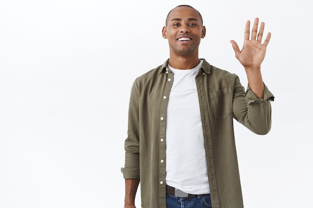 Portret van een vriendelijke afro-amerikaanse man in een casual outfit, die persoon in de menigte ziet, de aandacht van vrienden trekt, met opgeheven hand zwaait om hallo te zeggen