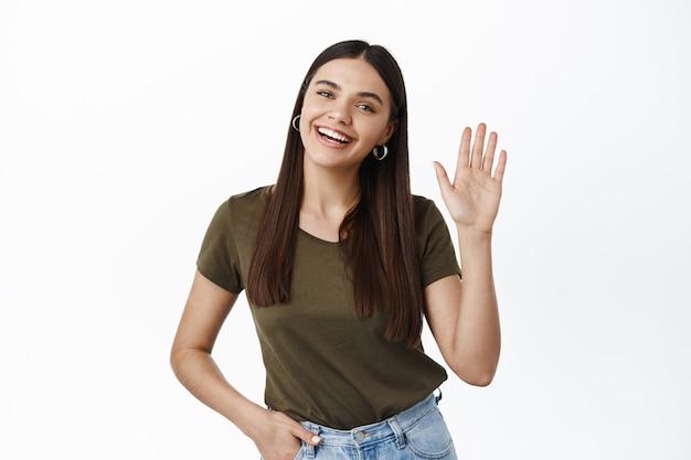 Portret van een vriendelijke jonge gelukkige vrouw die afziet van de hand om hallo te zeggen, je groet met een hallo gebaar, afscheid neemt, over een witte muur staat