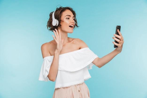 Portret van een vriendelijke jonge vrouw, luisteren naar muziek