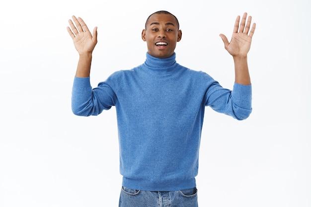 Portret van een vriendelijke, knappe afro-amerikaanse man die met opgeheven handen zwaait en tot ziens of hallo zegt