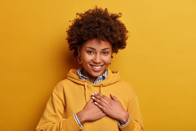 Portret van een vriendelijke vrouw met een donkere huidskleur maakt dankbaarheidsgebaar, spreekt dankbaarheid uit voor ontvangen compliment, draagt hoodie, geïsoleerd over gele muur, kreeg verrassing of lof, dankbaar zijn