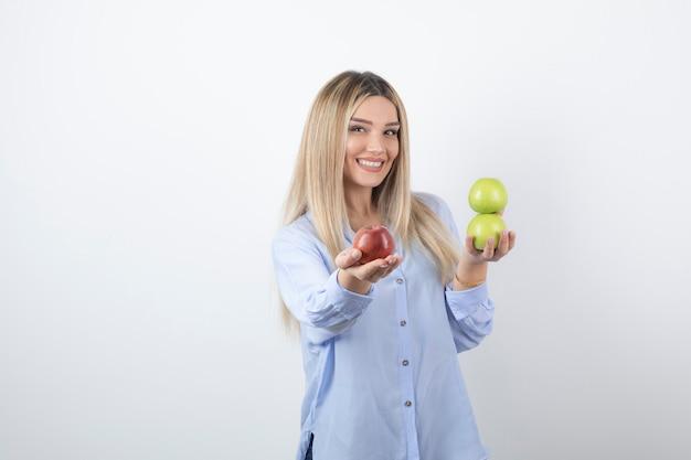 Portret van een vrij aantrekkelijk vrouwenmodel dat staat en verse appels vasthoudt.