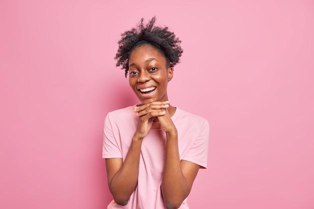Portret van een vrij donkere afro-amerikaanse vrouw houdt handen onder de kin en glimlacht breed