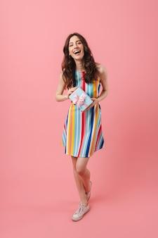 Portret van een vrij emotioneel blije schattige vrouw die zich voordeed over een roze muur met de huidige geschenkdoos.