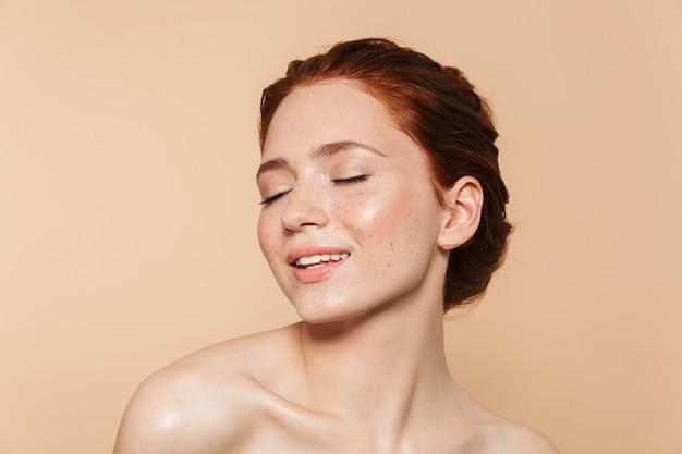Portret van een vrij gelukkig lachende geweldige jonge roodharige vrouw poseren geïsoleerd.