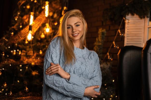 Portret van een vrij gelukkige jonge vrouw met een schattige glimlach in een trendy gebreid pak op de achtergrond van een feestelijke kerstboom met vintage slingers
