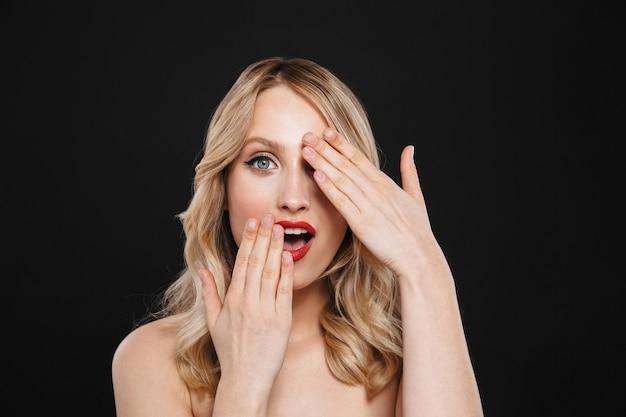 Portret van een vrij geschokte jonge blonde vrouw met heldere make-up rode lippen geïsoleerd poseren.