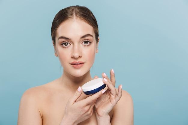 Portret van een vrij geweldige jonge vrouw die zich voordeed over een blauwe muur en voor haar huid zorgt met crème.