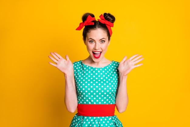 Portret van een vrij glamoureus vrolijk meisje met een gestippelde jurk, een goed nieuwsreactie, geïsoleerd over een levendige gele kleurachtergrond