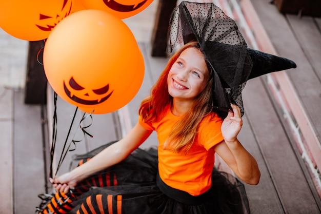 Portret van een vrij jong meisje in halloween-kostuum als een heks die op de trap van het huis zit en een bos oranje ballonnen vasthoudt. halloween-concept.