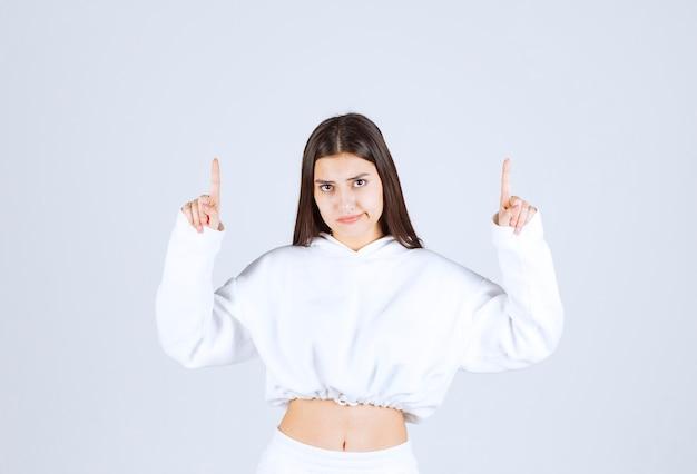Portret van een vrij jong meisjesmodel dat omhoog wijst.