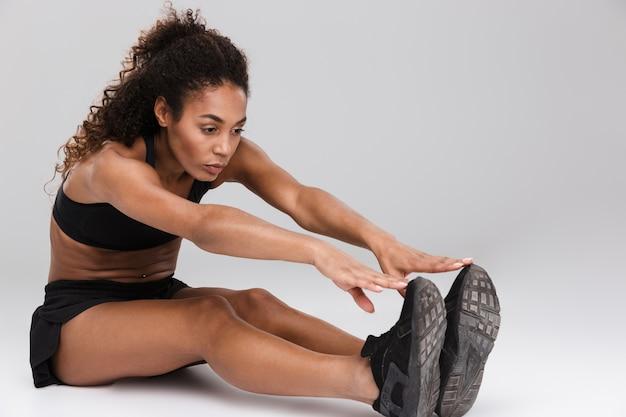 Portret van een vrij jonge afrikaanse sportvrouw die rekoefeningen doet die over grijze muur worden geïsoleerd