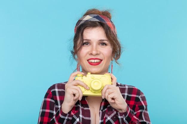 Portret van een vrij jonge positieve vrouw in een plaidoverhemd met een gele filmwijnoogst