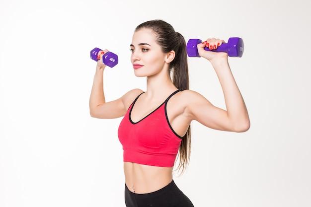Portret van een vrij jonge sportvrouw die oefeningen met domoren doet die op een witte muur worden geïsoleerd