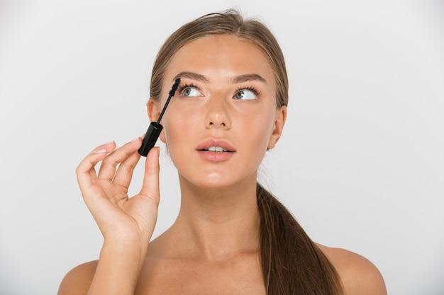 Portret van een vrij jonge topless geïsoleerde vrouw, mascara toe te passen