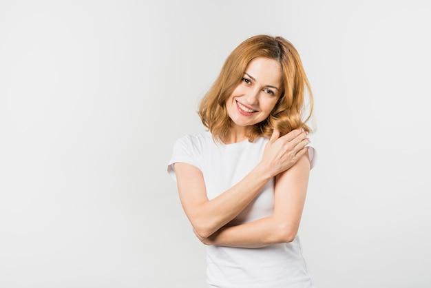 Portret van een vrij jonge vrouw die aan camera kijkt die op witte achtergrond wordt geïsoleerd