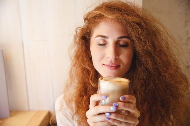 Portret van een vrij jonge vrouw die haar koffiedrank ruikt