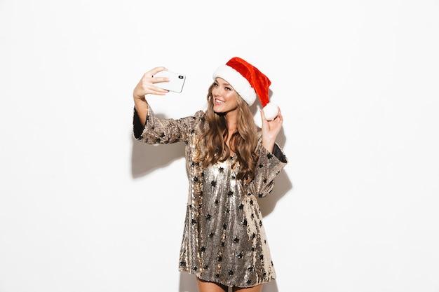 Portret van een vrij jonge vrouw die rode hoed draagt die nieuwjaar viert dat over witte ruimte wordt geïsoleerd