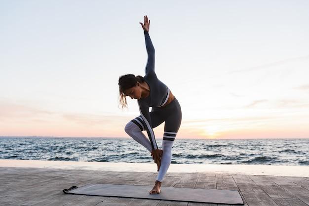 Portret van een vrij jonge vrouw die yogaoefeningen doet