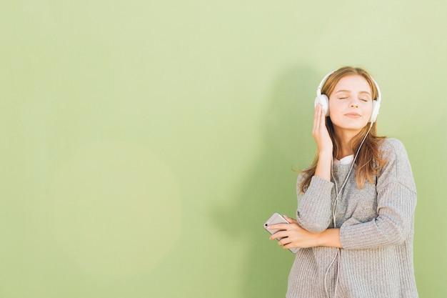 Portret van een vrij jonge vrouw het luisteren muziek op hoofdtelefoon door mobiele telefoon tegen munt groene achtergrond