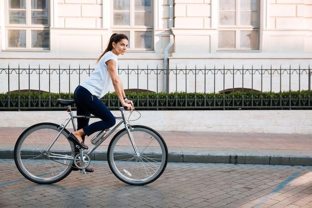 Portret van een vrij jonge vrouw op fiets in de stadsstraat