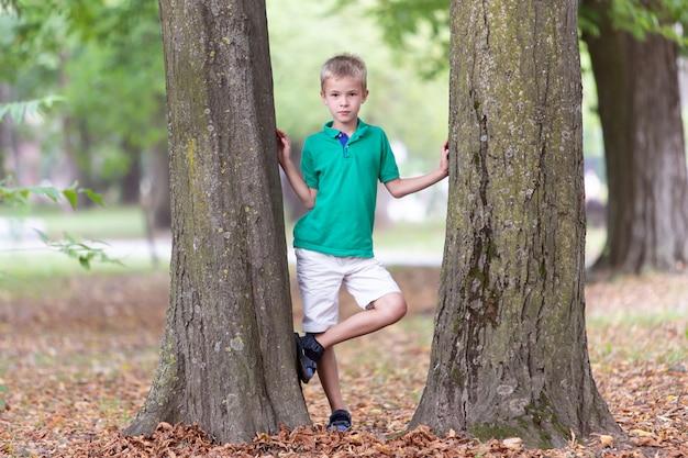 Portret van een vrij leuke kindjongen die dichtbij grote boomboomstam zich in de zomerpark in openlucht bevinden.