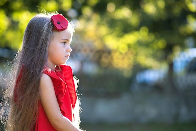 Portret van een vrij modieus kindmeisje in een rode jurk die geniet van een warme zonnige zomerdag.