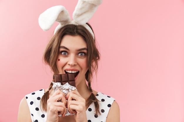 Portret van een vrij mooi meisje dat konijntjesoren draagt die geïsoleerd staan, chocolade eten