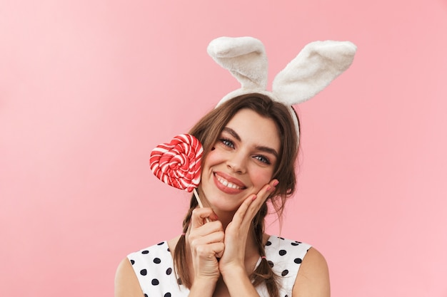 Portret van een vrij mooi meisje dat konijntjesoren draagt die geïsoleerd staan, grimassen, lolly houden