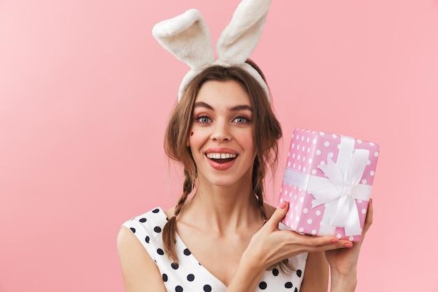 Portret van een vrij mooi meisje dat konijntjesoren draagt die zich geïsoleerd bevinden, die giftdoos houden