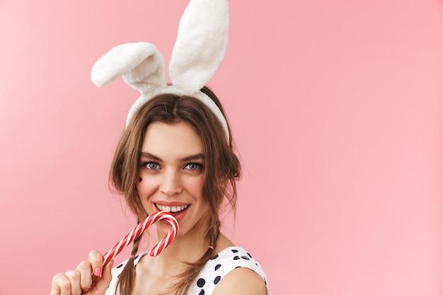 Portret van een vrij mooi meisje dat konijntjesoren draagt die zich geïsoleerd bevinden, grimassen, suikergoedriet houden