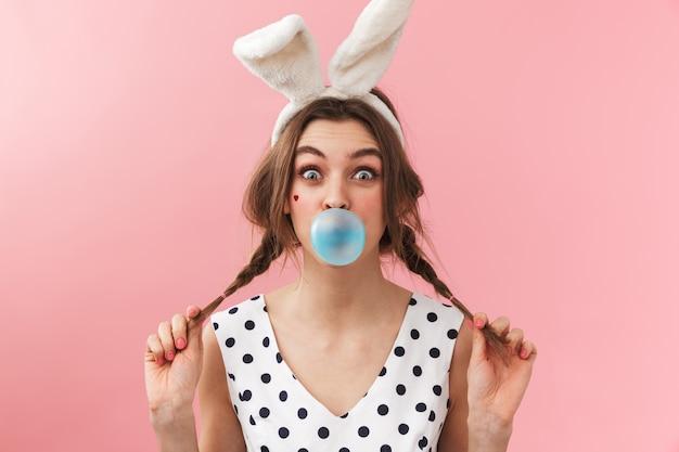 Portret van een vrij mooi meisje dat konijntjesoren draagt die zich geïsoleerd bevinden, kauwgom kauwen