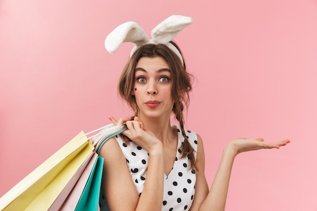 Portret van een vrij mooi meisje dat konijntjesoren draagt die zich geïsoleerd bevinden, met boodschappentassen