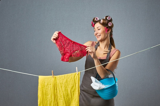 Portret van een vrij retro vrouw die slipje in een koord op grijze muur ophangt. fanny huisvrouw krulspelden drogen van kleren. huishoudelijk concept.
