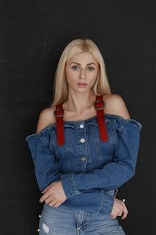 Portret van een vrij sexy jonge blonde vrouw in een stijlvolle denim kleding met haar armen gevouwen vormt in de buurt van een zwarte muur. Premium Foto