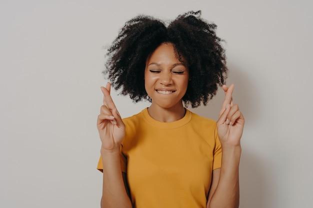 Portret van een vrij vrolijk afrikaans meisje dat geïsoleerd staat over een witte studioachtergrond met kopieerruimte, vingers gekruist houdt voor geluk, met gesloten ogen die onderlip bijten terwijl ze een wens doen