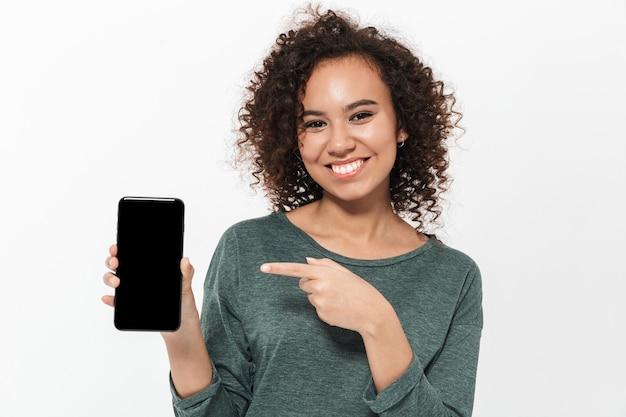 Portret van een vrij vrolijk, casual afrikaans meisje dat geïsoleerd over een witte muur staat en een mobiele telefoon met een leeg scherm presenteert
