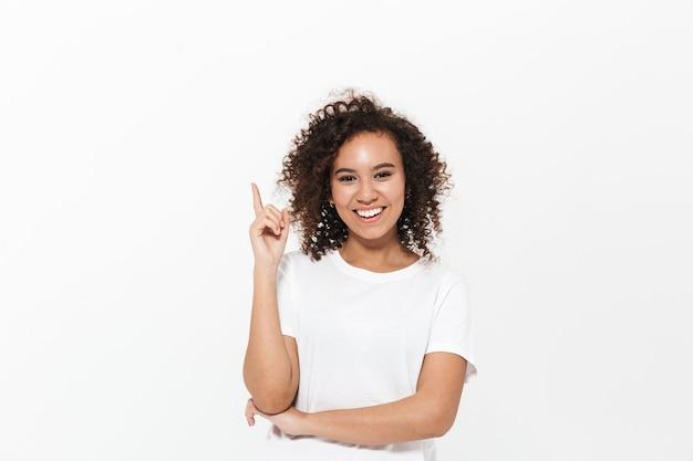 Portret van een vrij vrolijk, casual afrikaans meisje dat geïsoleerd over een witte muur staat en kopieerruimte presenteert